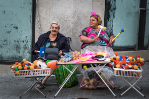 Two woman sell plastic hammers in the streets of Porto's historical centre. Traditionally people celebrating São João in Porto used to beat each other in the head with leeks, because leek was considered a symbol of fertility. It is believed that this custom has ancient origins tracing back to pre-Christian paganism. In the 70s leeks were replaced with plastic hammers, which have become an icon of the modern day festival.